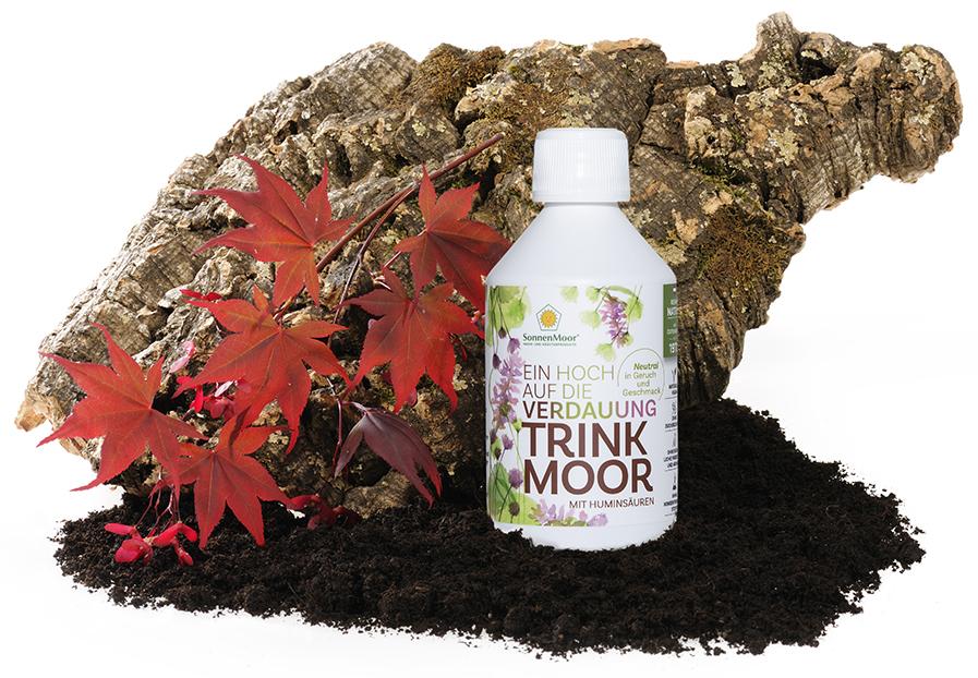 Eine Flasche SonnenMoor Trinkmoor auf dunklem Moor stehend vor einer Wurzel. Links vorne ein Zweig mit roten Blättern