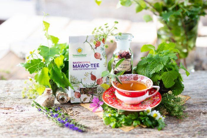 ein Tasse SonnenMoor MAWO Tee umgeben von Kräutern und Blüten